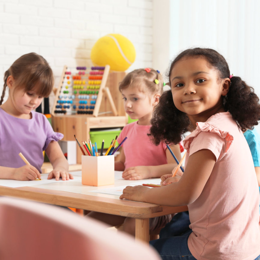 a kid facing in camera while two kids are drawing