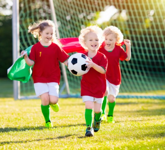 Kids play football on outdoor field