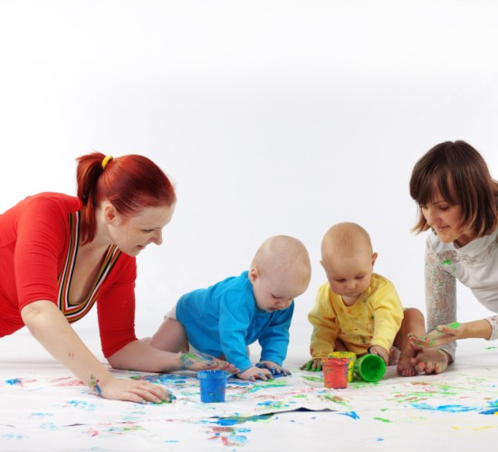 Two babies painting with parents