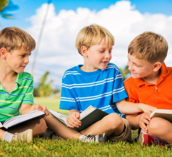 Group of Happy Kids Reading Books Outside