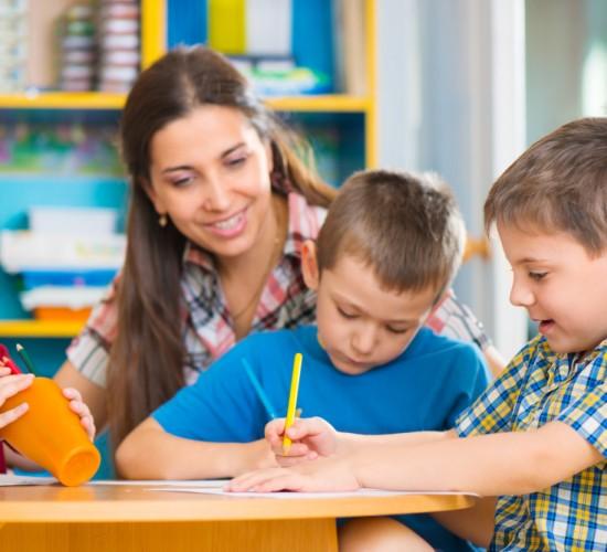 Cute little children drawing with teacher at preschool class