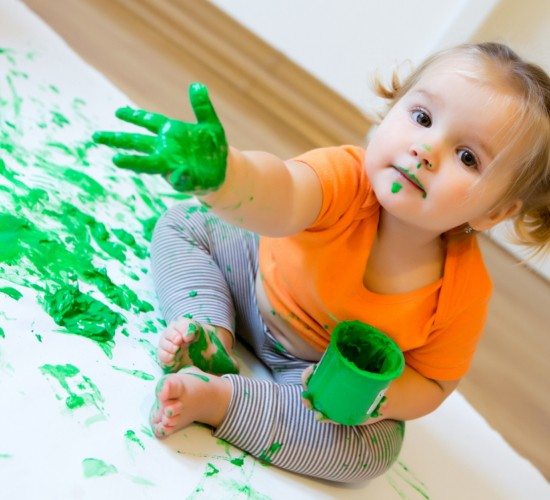 Little girl with green paint