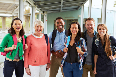 group of cheerful teachers hanging out in school corridor